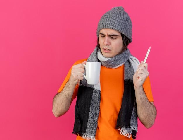 Confuso giovane uomo malato che indossa un cappello invernale con sciarpa tenendo il termometro guardando la tazza di tè in mano isolato su sfondo rosa