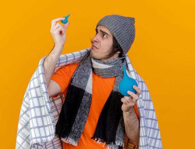 Confuso giovane uomo malato che indossa cappello invernale con sciarpa avvolta in plaid sollevando e guardando clistere isolato su sfondo arancione