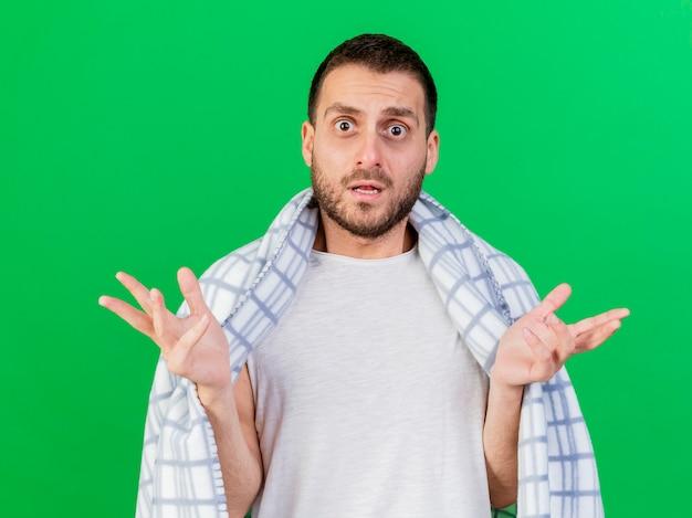 Confuso giovane uomo malato avvolto in plaid e diffondendo le mani isolate su sfondo verde