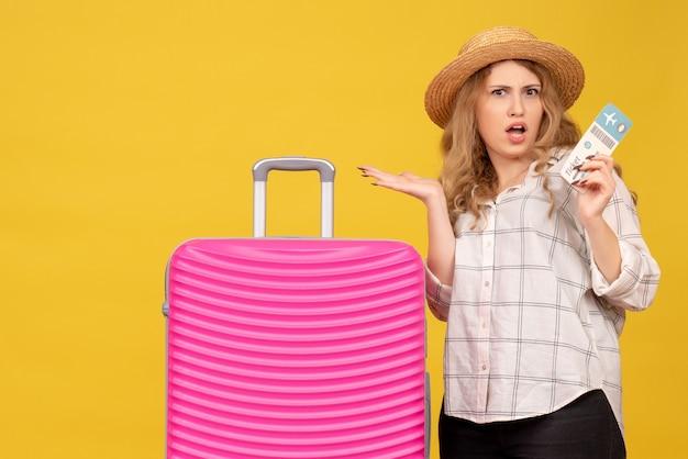 Confusa giovane donna che indossa un cappello che mostra il biglietto e in piedi vicino alla sua borsa rosa