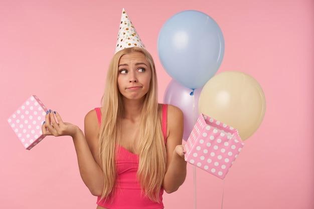 Confusa giovane donna dai capelli lunghi con acconciatura casual in posa su sfondo rosa con presente nelle sue mani, celebrando le vacanze e disimballando i regali, guardando da parte con le labbra piegate