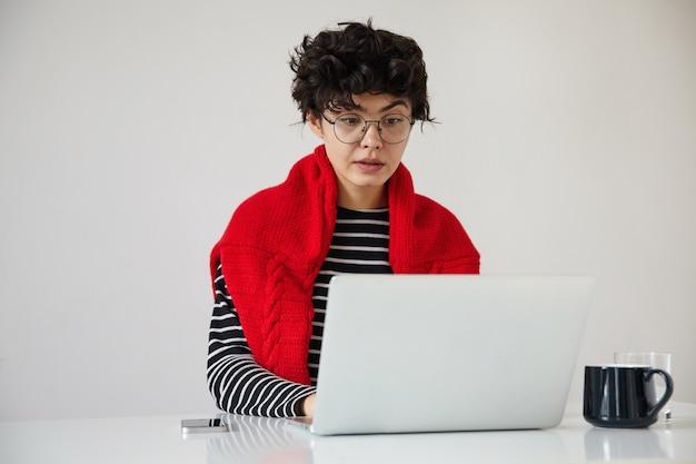 Смущенная молодая милая кудрявая брюнетка с короткой стрижкой сидит за столом с современным ноутбуком и поднимает бровь, глядя на экран с озадаченным лицом, изолированным на белом фоне