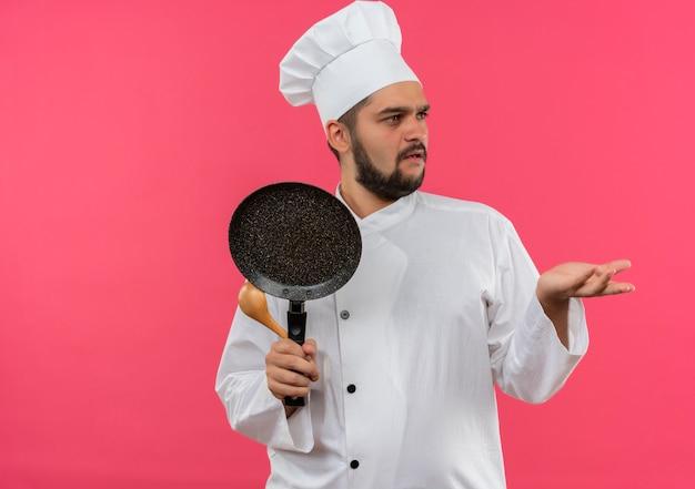 Смущенный молодой мужчина-повар в униформе шеф-повара держит сковороду и ложку, глядя в сторону и показывая пустую руку, изолированную на розовой стене с копией пространства