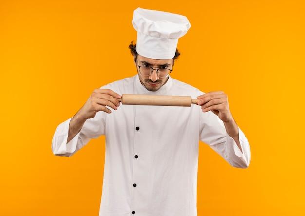요리사 유니폼과 안경을 들고 롤링 핀을보고 혼란 스 러 워 젊은 남성 요리사