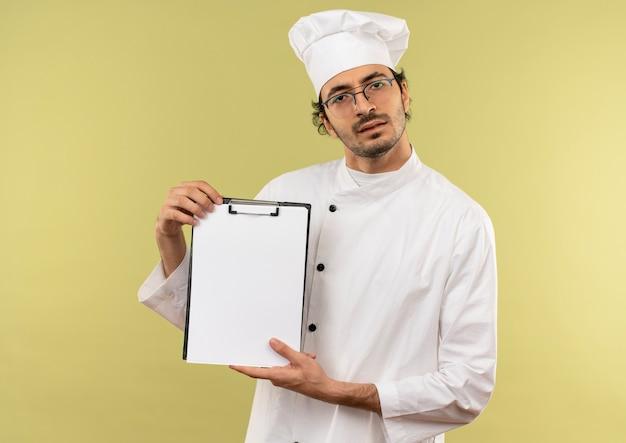 Confuso giovane cuoco maschio che indossa l'uniforme dello chef e bicchieri tenendo appunti