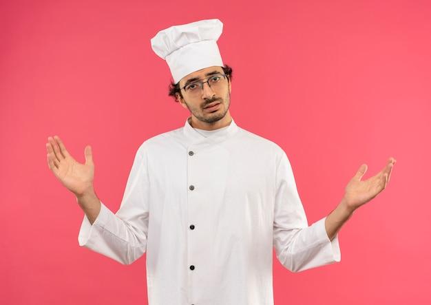 Confuso giovane cuoco maschio che indossa la divisa da chef e bicchieri allarga le mani