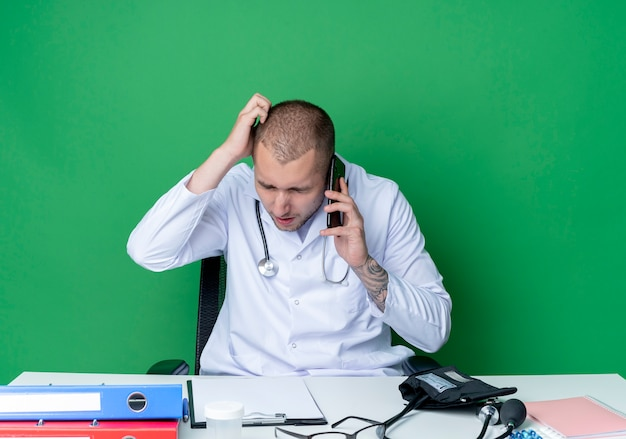 Confuso giovane medico maschio indossa abito medico e stetoscopio seduto alla scrivania con strumenti di lavoro parlando al telefono con la mano sulla testa e gli occhi chiusi isolati su verde
