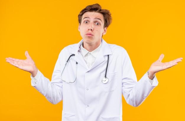 주황색 벽에 격리된 손을 펼치고 있는 의료 가운을 입은 혼란스러운 젊은 남성 의사