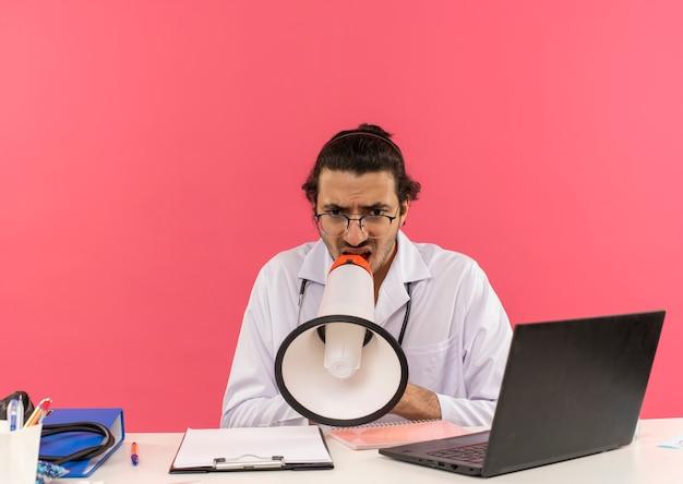 책상에 앉아 청진기와 의료 가운을 입고 의료 안경 혼란 젊은 남성 의사