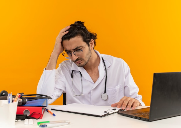 Confuso giovane medico maschio con occhiali medici che indossano accappatoio medico con stetoscopio seduto alla scrivania Foto Gratuite