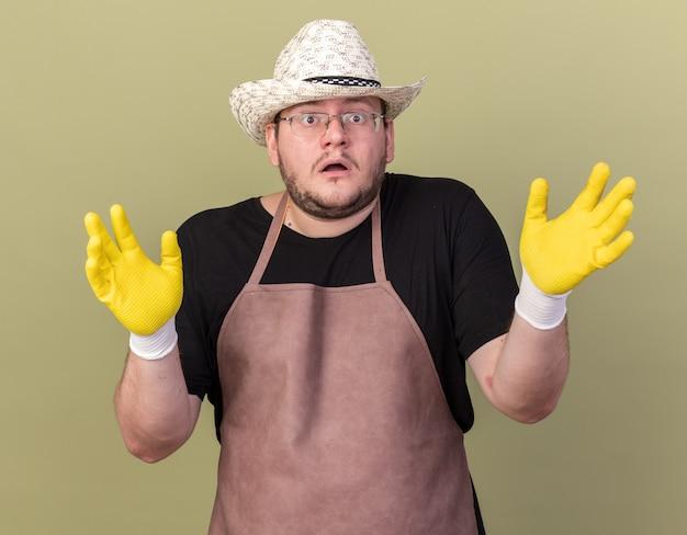 オリーブ グリーンの壁に手を広げてガーデニング帽子と手袋を身に着けている混乱した若い男性庭師