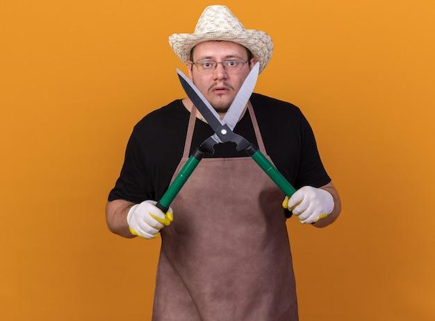 Giardiniere maschio giovane confuso indossando guanti e cappello da giardinaggio tenendo i clippers intorno al viso isolato sulla parete arancione