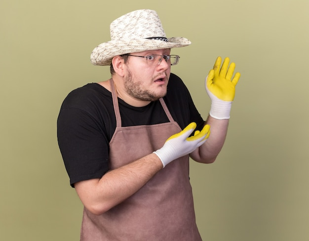 Il giovane giardiniere maschio confuso che indossa il cappello e i guanti di giardinaggio indica dietro isolato sulla parete verde oliva con lo spazio della copia