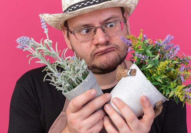 ピンクの壁に隔離された植木鉢の花を持って見ているガーデニング帽子をかぶった若い男性の庭師が混乱している