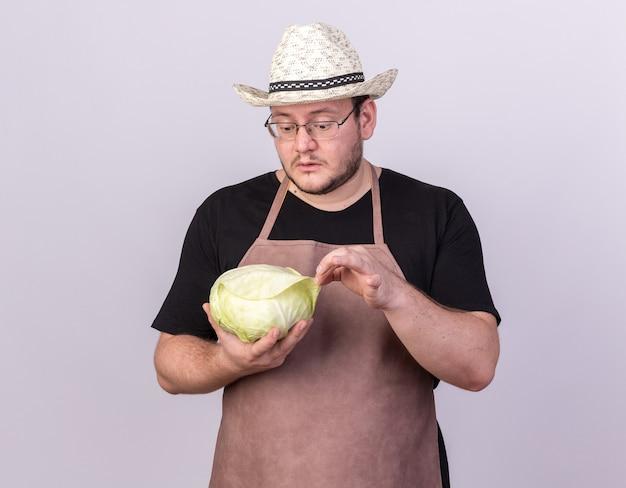 Confuso giovane giardiniere maschio che indossa cappello da giardinaggio tenendo e guardando cavolo isolato su muro bianco
