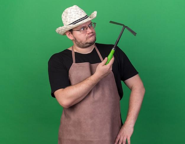 Giardiniere maschio giovane confuso che porta il cappello di giardinaggio che tiene e che esamina il rastrello della zappa isolato sulla parete verde