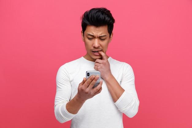 Giovane confuso che morde il dito che tiene e che guarda il telefono cellulare