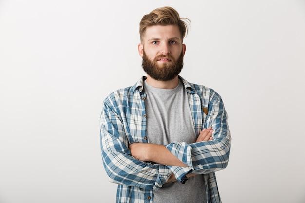 Смущенный молодой человек, одетый в клетчатую рубашку, стоящий изолированно