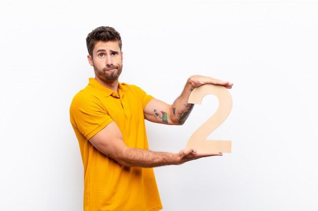 Растерянный молодой человек держит номер 2