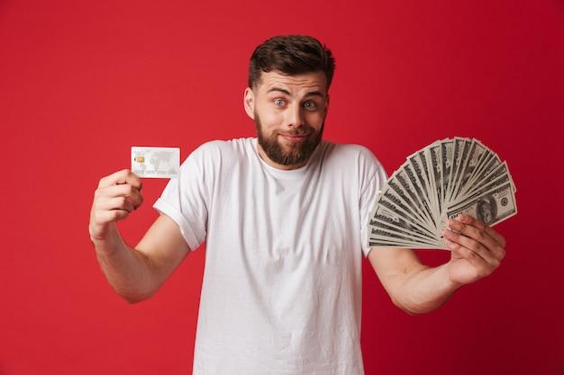 Путать молодой человек, держащий деньги и кредитную карту.