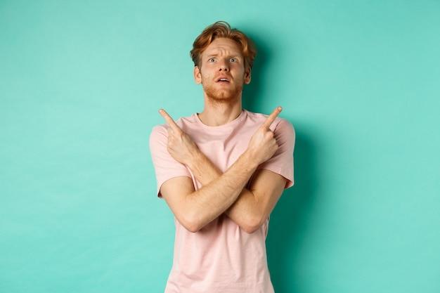 ターコイズブルーの背景の上に立って、見上げて、指を横に向けて、困惑していると感じて、決定できない、tシャツを着た混乱した若い男。