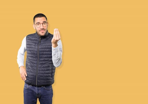 理解できないのイタリアのジェスチャーを作る混乱の若い男