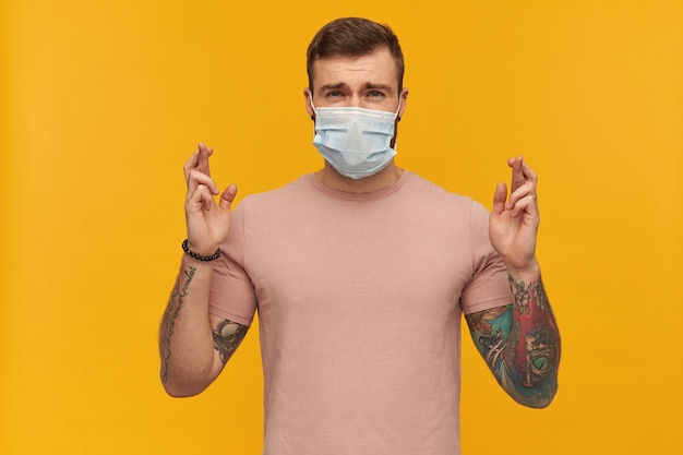 Confused young man in pink tshirt and virus protective mask on face against coronavirus with beard and tattoo keeps fingers crossed and making a wish over yellow wall