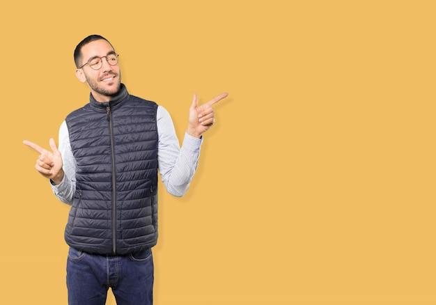 Confused young man poiting in both directions