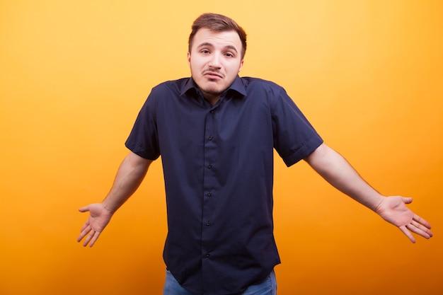 Смущенный молодой человек поднимает плечи. демонстрация реакции