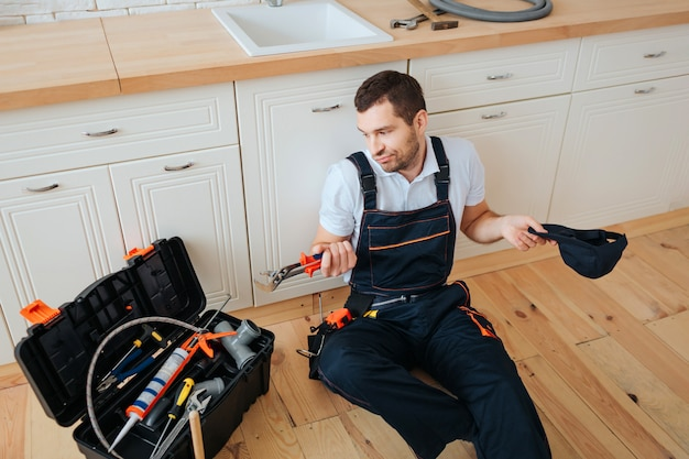 Confused young man sits on floor in kitchen and looks at toolbox