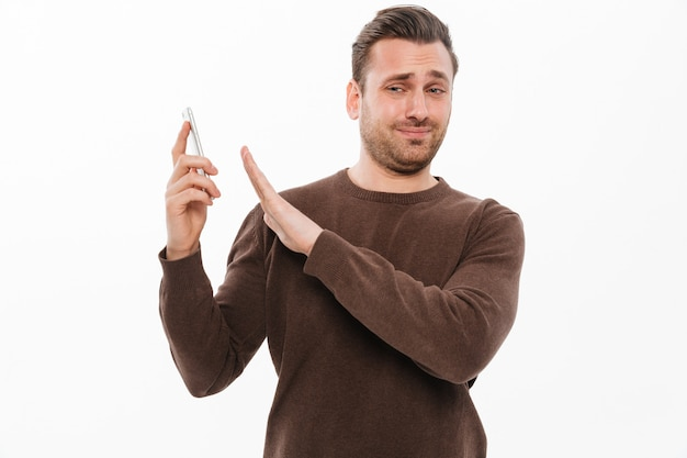 Confused young man talking by mobile phone
