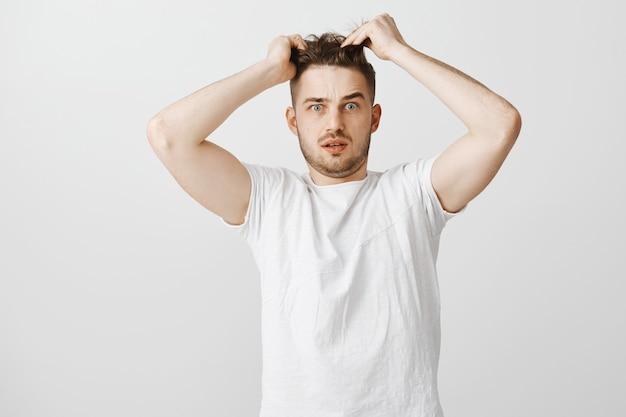 混乱している若い男が髪に触れる、新しい散髪が必要