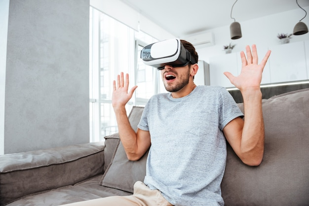 Confused young man wearing virtual reality device while sitting on sofa