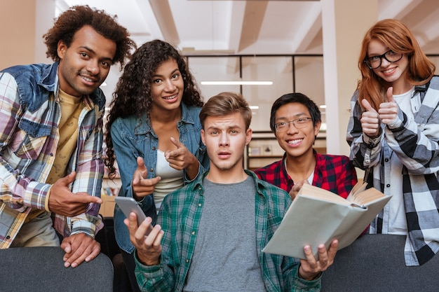 Confused young man with book and cell phone with his happy friends