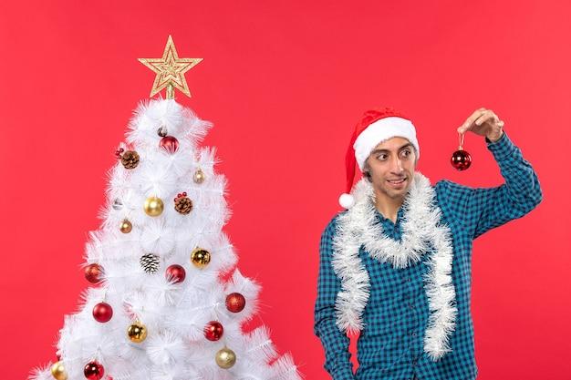 파란색 벗겨진 셔츠에 산타 클로스 모자와 장식 액세서리를 보여주는 혼란 젊은 남자