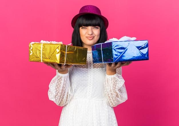 분홍색 벽에 격리된 선물 꾸러미를 들고 파티 모자를 쓴 혼란스러운 젊은 파티 소녀
