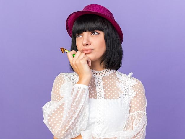 紫色の壁に分離されたあごに触れて見上げるパーティーホーンを保持しているパーティーハットを身に着けている混乱した若いパーティーの女の子