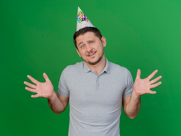 緑に分離された手を広げて誕生日キャップを身に着けている混乱した若いパーティー男