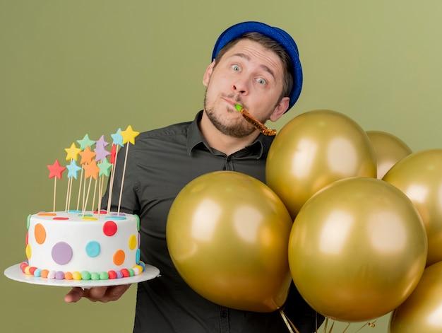 올리브 그린에 고립 된 파티 송풍기를 불고 풍선과 함께 케이크를 들고 검은 셔츠와 파란색 모자를 쓰고 혼란 된 젊은 파티 남자