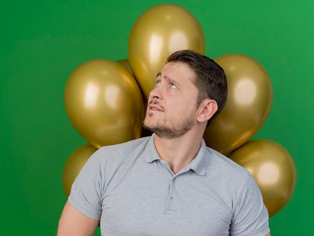 Ragazzo di partito giovane confuso indossa una camicia grigia in piedi davanti a palloncini isolati su verde
