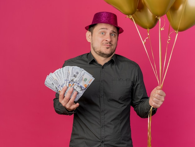 Confused young party guy wearing pink hat holding cash with balloons isolated on pink