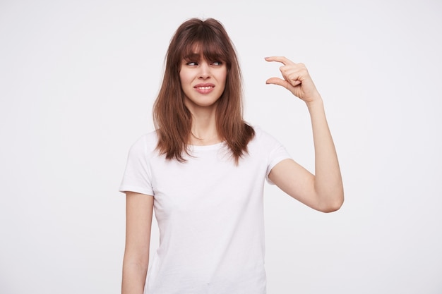 Confused young pretty brown haired lady with wild hairstyle looking at her raised hand with displeased face, being disappointed about small size, standing over white wall