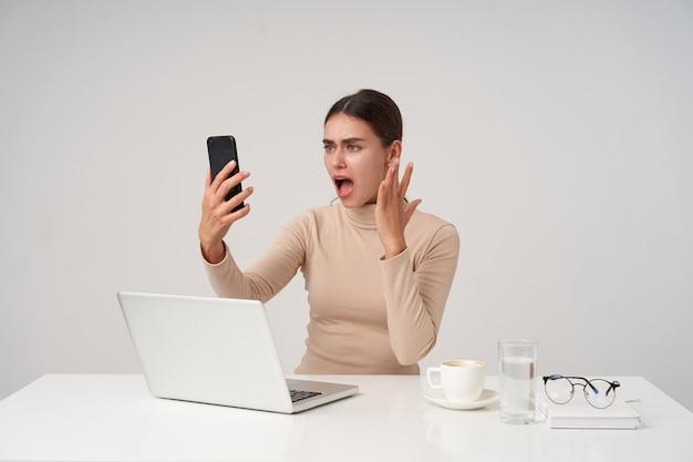 Смущенная молодая симпатичная брюнетка в бежевом полоне сидит за столом над белой стеной, ведет неприятный видео-разговор и эмоционально поднимает руку