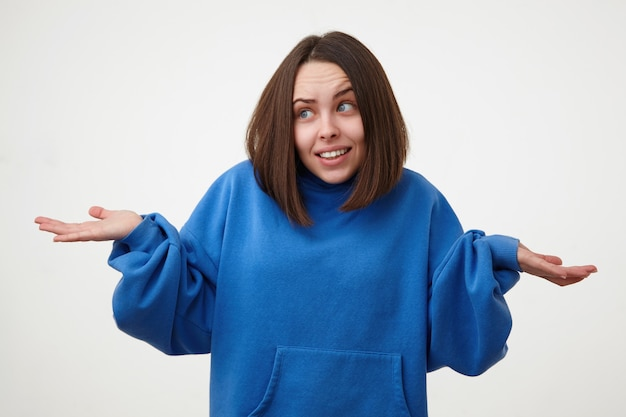 白い壁に隔離された、脇を見て少し笑っている間、困惑して手を上げている短い髪の混乱した若いかなりブルネットの女性
