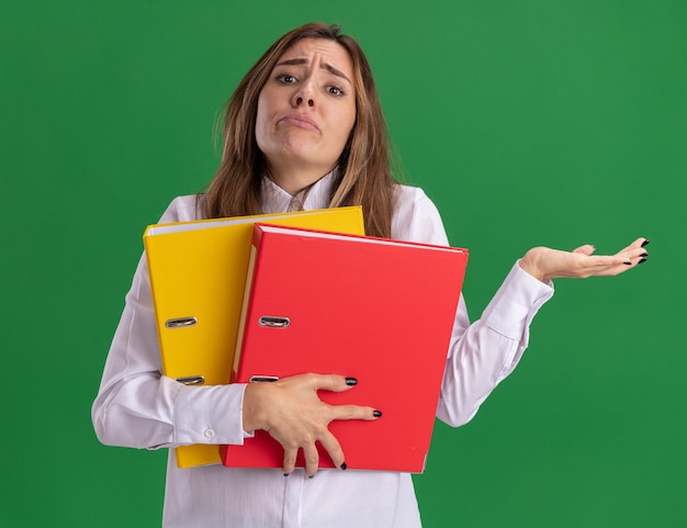 Confused young pretty caucasian girl holds file folders and keeps hand open on green