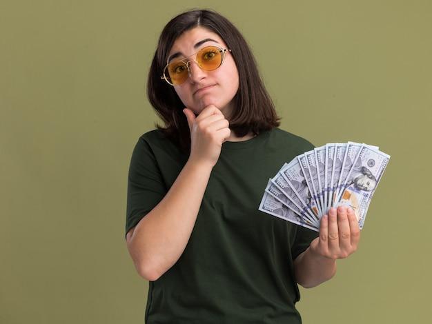 Смущенная молодая симпатичная кавказская девушка в солнцезащитных очках кладет руку на подбородок и держит деньги на оливково-зеленом