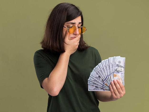 Смущенная молодая симпатичная кавказская девушка в солнцезащитных очках кладет руку на подбородок, держа и глядя на деньги на оливково-зеленом