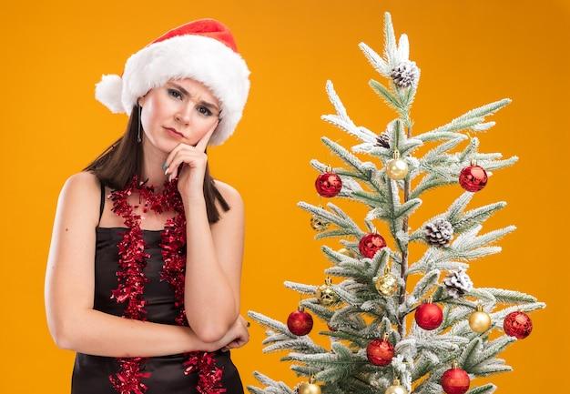 オレンジ色の背景で隔離のカメラを見てあごに手を保ちながら装飾されたクリスマスツリーの近くに立っている首の周りにサンタの帽子と見掛け倒しの花輪を身に着けている混乱した若いかなり白人の女の子