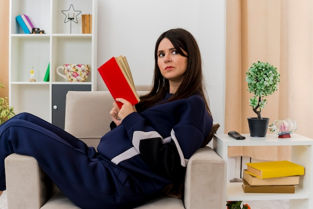 Confused young pretty caucasian woman sitting on armchair in designed living room holding book and looking at side