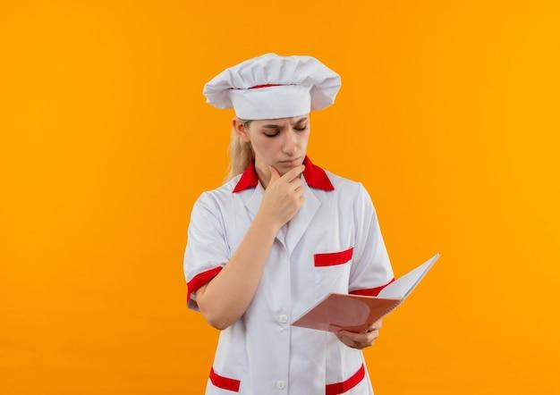 Смущенный молодой симпатичный повар в униформе шеф-повара держит и смотрит в блокнот с рукой на подбородке, изолированной на оранжевой стене